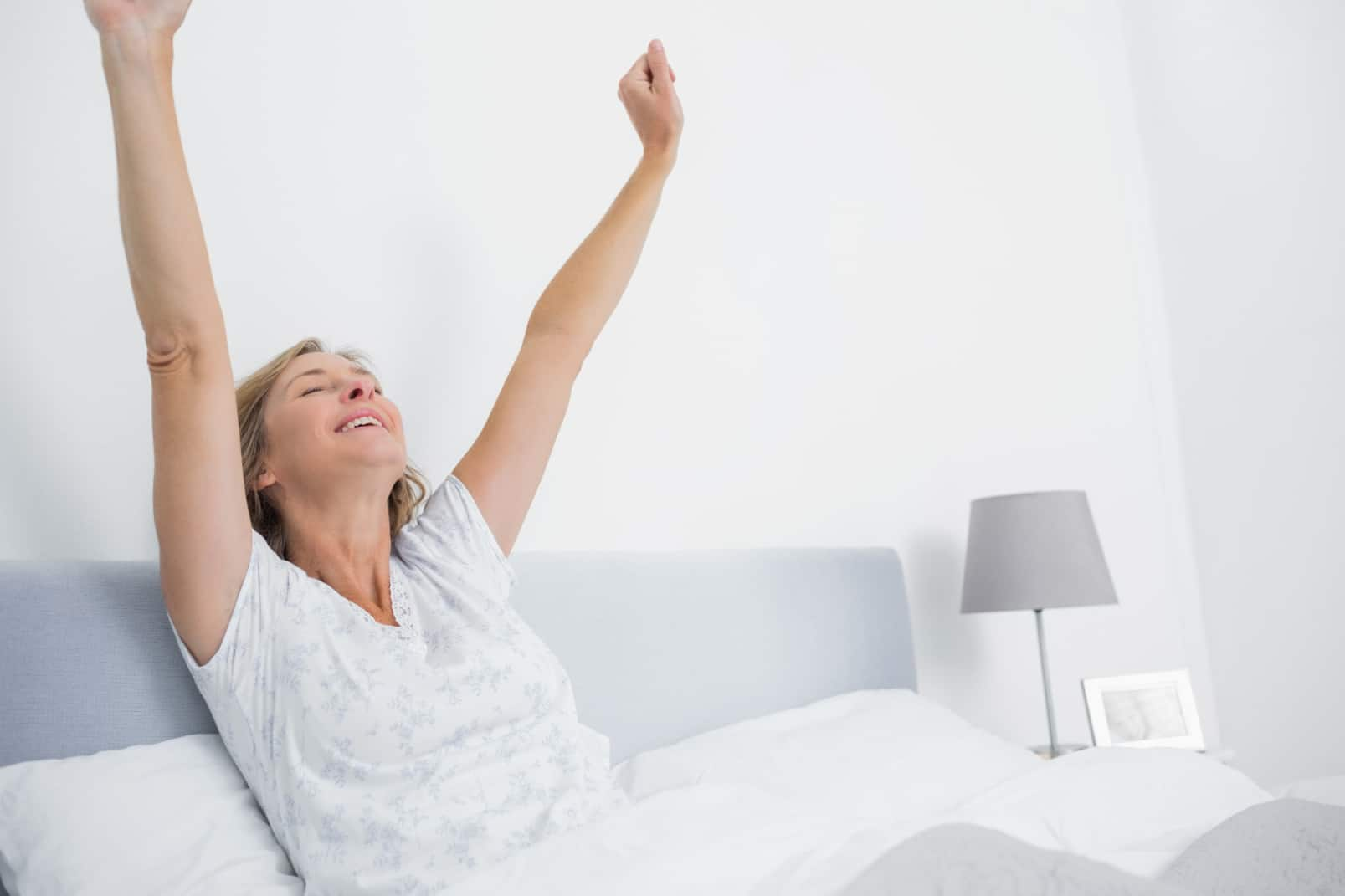 Well rested blonde woman stretching in bed and smiling in bedroom at home
